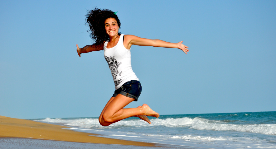 girl jumping up at the beach